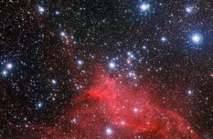 This fantastic red cloud of gas and dust and the young stars scattered around it are all part of an open star cluster called NGC 3572. Credit: ESO